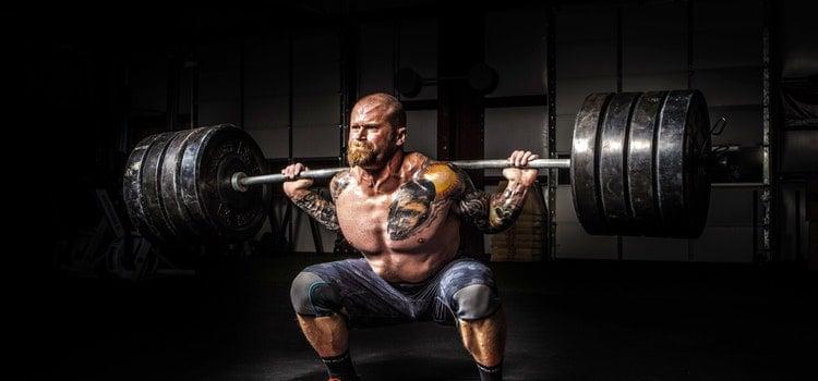 muskulöser Mann mit Tattoos hebt ca. 200Kg Gewicht