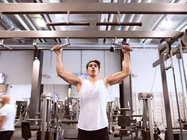74320484 – hispanic man in gym doing pull-ups on horizontal bar