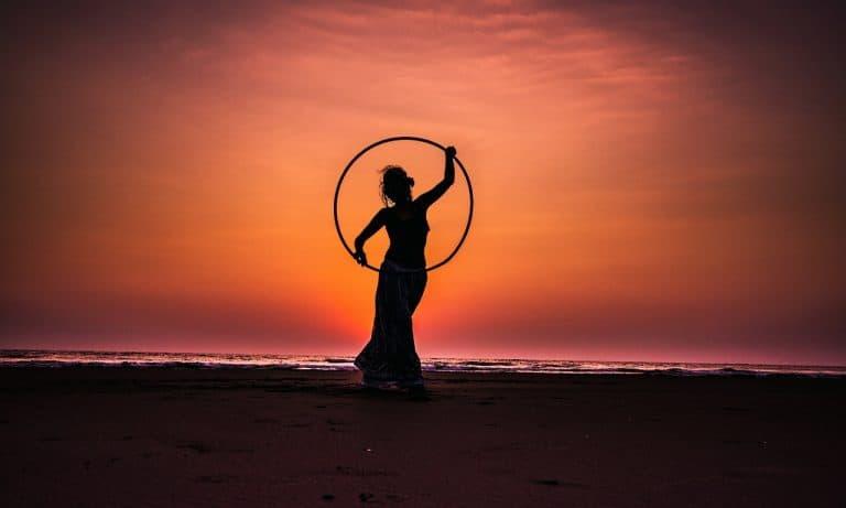 Frau mit Hula-Hoop-Reifen vor Sonnenuntergang