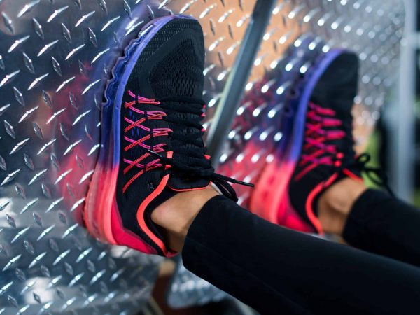 62759278 – close up shoes of a fit young woman doing leg press in the gym.
