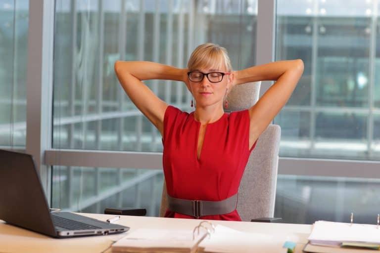 Frau am Schreibtisch mit hinter dem Kopf verschränkten Armen
