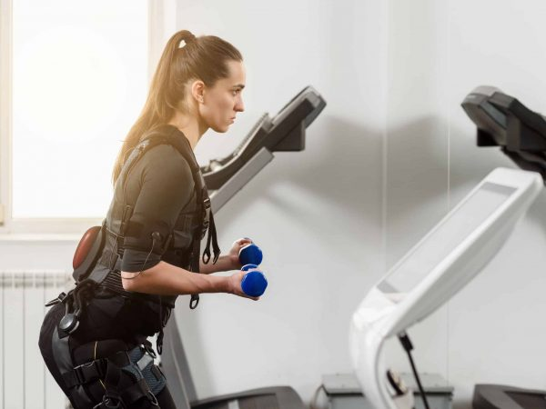 Woman in electro muscular stimulation suit training with dumbbells
