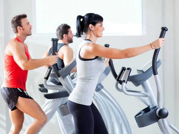 11982197 – man and woman with elliptical cross trainer in sport fitness gym club