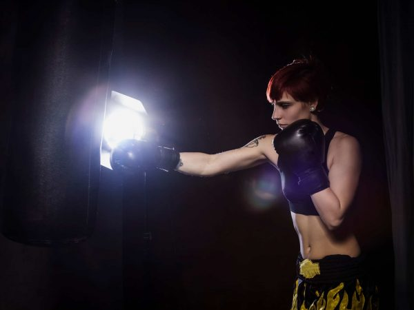Athlete boxer woman punching a punching bag with dramatic lighting in a dark studio