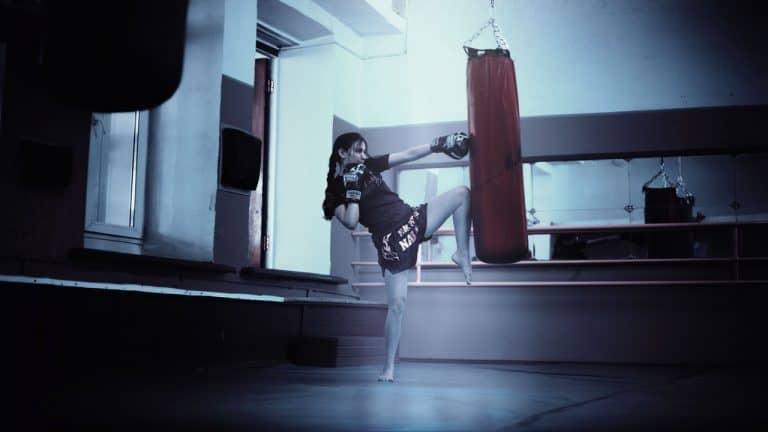 Frau kickt Boxsack