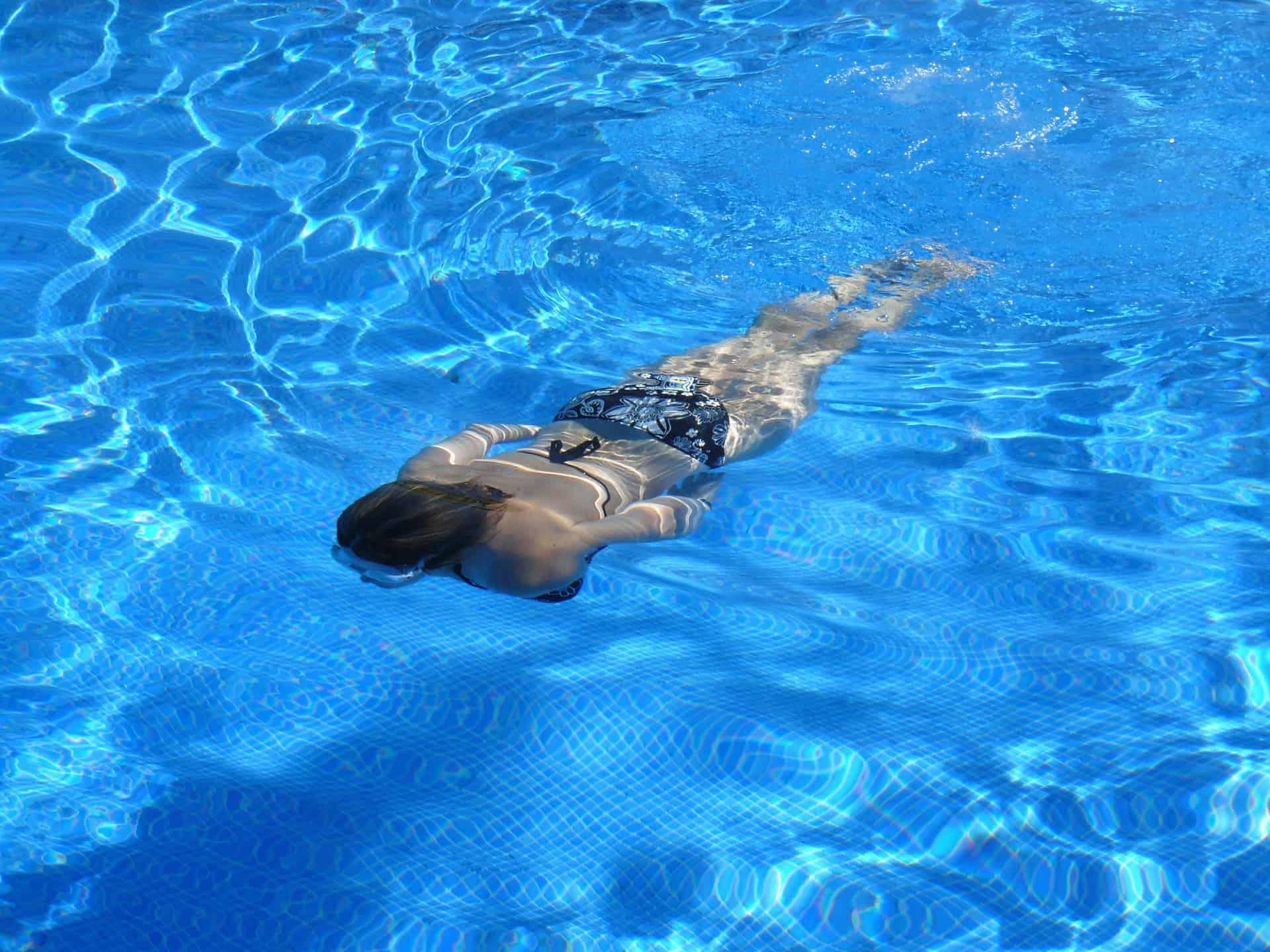 Frau taucht in Schwimmbecker