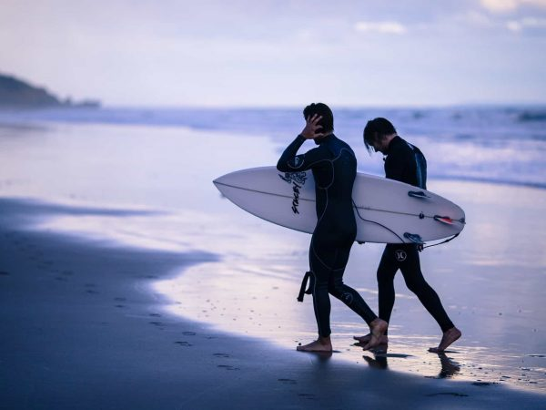 Zwei Surfer in Neoprenanzügen am Strand