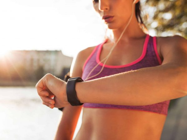 Young fitness woman looking at her smart watch while taking a break from outdoor workout. Sportwoman checking pulse on fitness smart watch device.