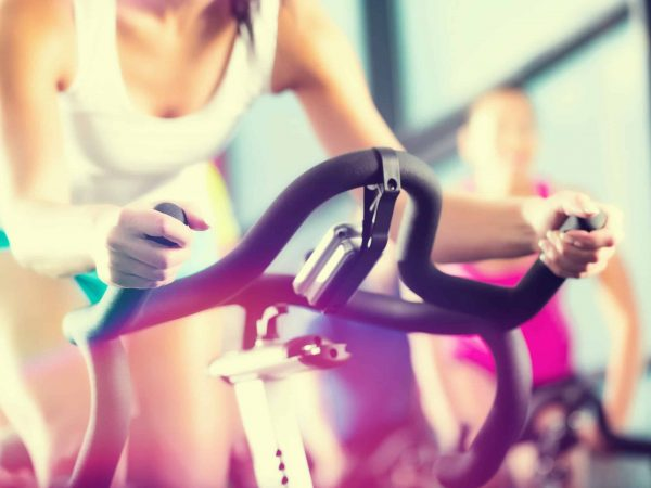 Young People – group of women and men – doing sport Spinning in the gym for fitness