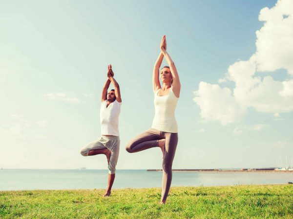 fitness, sport, friendship and lifestyle concept – smiling couple making yoga exercises outdoors