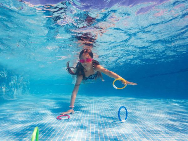 Preteen girl in pink goggles collecting colorful aqua rings, exercising during underwater swimming lesson in the pool