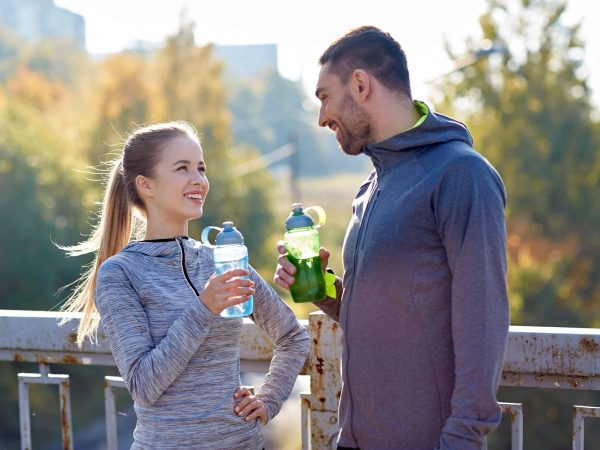 fitness, sport, people and lifestyle concept – smiling couple with bottles of water outdoors