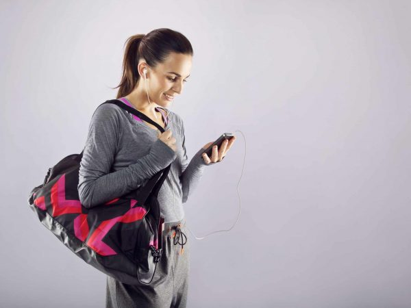 Good looking female athlete with a sports bag listening to music on her mobile phone. Fitness woman in sports clothing going to gym on grey background
