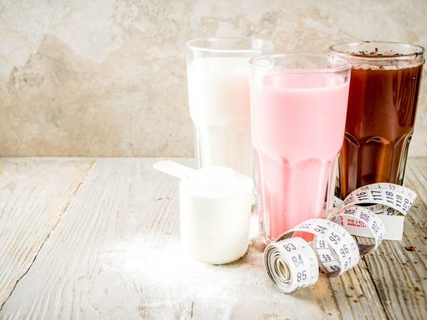 Healthy organic diet drink. Chocolate, berry and vanilla protein shakes. Non dairy protein vegan cocktails. With measuring tape. Concept of weight loss, fitness, healthy lifestyle.