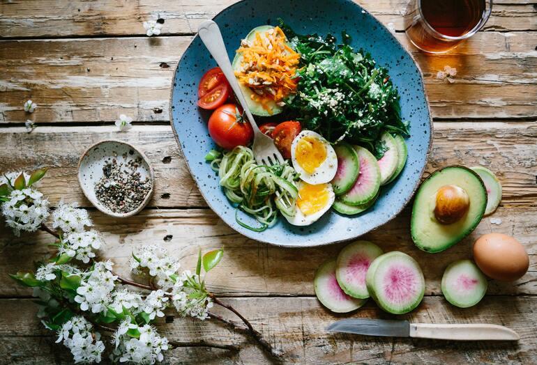 Ein blauer Teller mit verschiedenen, gesunden Lebensmitteln wie Avocado, Ei, Tomaten.