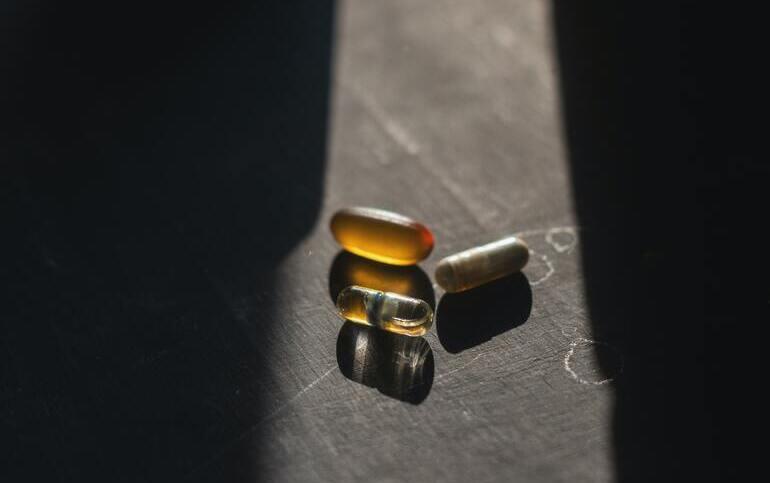 Drei verschiedene Kapseln liegen in einem Sonnenstrahl, der in ein dunkles Zimmer hineinscheint.