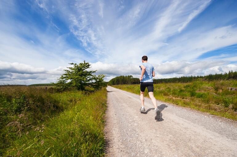 Mann joggt einen Weg mit Wiesen entlang.
