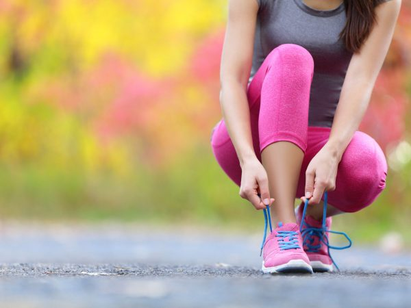 40349904 – running shoes – woman tying shoe laces. closeup of female sport fitness runner getting ready for jogging outdoors on forest path in late summer or fall.