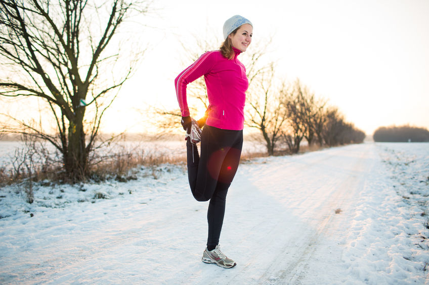 Young woman stretching while running outdoors on a cold winter evening